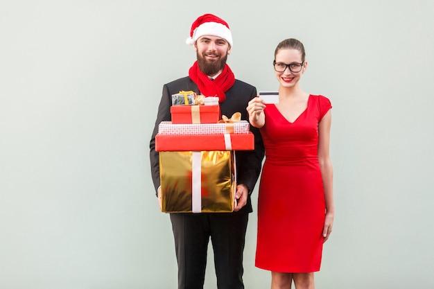 Coppia di felicità dopo lo shopping. mostrando regali, scatola e carta sconto. toothy sorridente e guardando la fotocamera. foto in studio