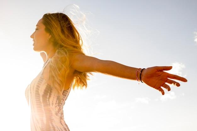 Felicità e libertà concetto di gioia con la giovane bella ragazza caucasica a braccia aperte e godersi il sole
