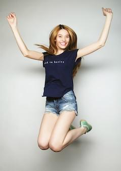 Felicità, libertà, movimento e concetto di persone - giovane donna sorridente che salta in aria