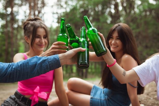 Felicità. gruppo di amici che tintinnano le bottiglie di birra durante il picnic nella foresta estiva.