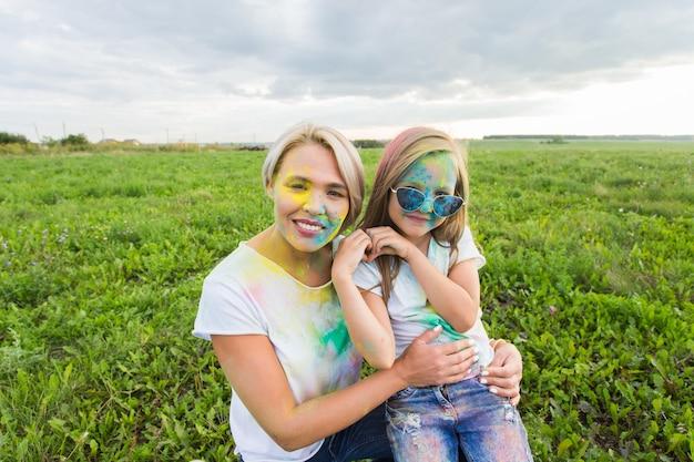 Felicità, festival di holi e concetto di vacanze - madre e figlia ricoperte di polvere colorata