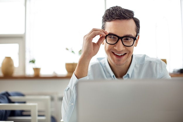 Felicità dentro di me. attraente uomo dai capelli scuri allegro sorridente e lavorando sul suo laptop e toccando gli occhiali mentre era seduto al tavolo