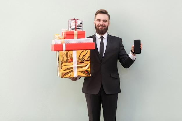 Manager della felicità che tiene e mostra alla telecamera scatola di natale e telefono