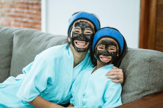 Felicità della madre e del bambino quando si usano maschere facciali di argilla insieme mentre si è seduti sul divano