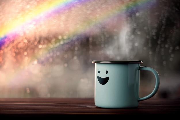 Felicità e mente positiva, concetto di salute mentale. godersi il caffè con un cartone animato sorridente, pioggia sfocata con arcobaleno come vista esterna. sorridi in un giorno di pioggia