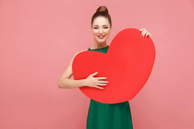 La donna di felicità abbraccia il grande cuore rosso, sorridente a trentadue denti. concetto di emozione e sentimenti di espressione. studio girato, isolato su sfondo rosa