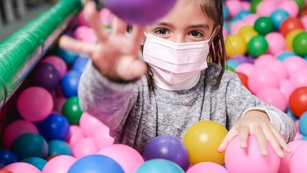 Ragazza felice di 5 anni con la maschera in una piscina di palline che lancia le palle alla macchina fotografica