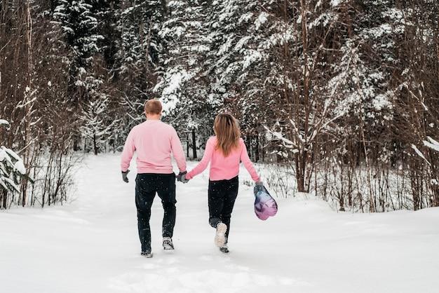 Felice coppia attiva nella foresta invernale, giorno di moroz, stile di vita.