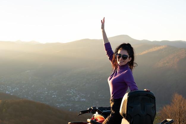 Autista femminile attivo felice che si gode la guida estrema su una moto quad atv in montagne autunnali