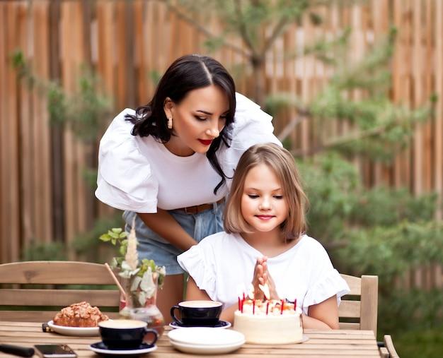 La ragazza adorabile felice con la mamma festeggia con la torta di compleanno nella terrazza del caffè. 10 anni festeggiano il compleanno.