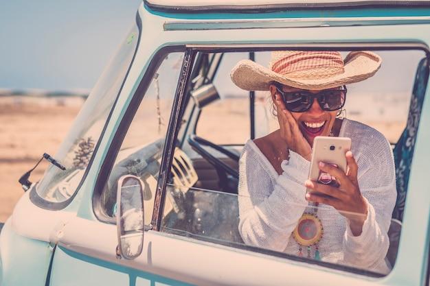 Felice giovane e bella donna adulta all'interno di un vecchio furgone blu alla moda vintage che si gode il viaggio in viaggio