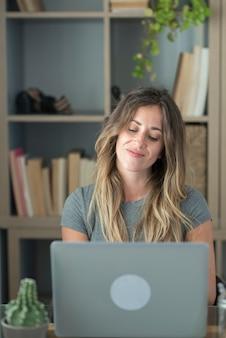 La donna caucasica adulta felice nello sguardo professionale allo schermo del laptop funziona in linea sul gadget dall'ufficio domestico. il computer di uso femminile giovane sorridente naviga in internet sul dispositivo. concetto di tecnologia.