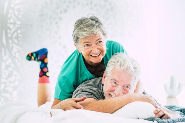 Felice coppia adulta gioca e si diverte sul letto di casa la mattina