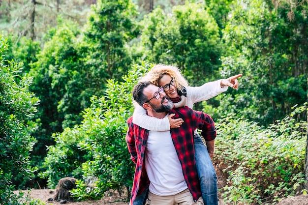 Felice coppia adulta godersi l'attività di svago all'aperto della natura insieme all'uomo che trasporta una bella donna allegra con una foresta verde sullo sfondo - concetto di felicità e amore per le persone