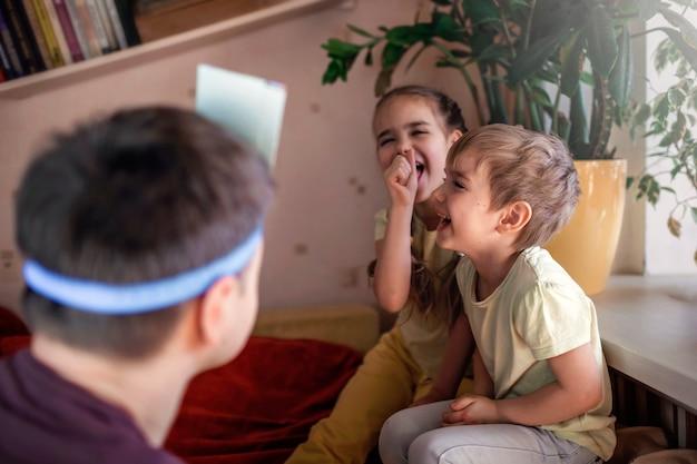 Felice padre adulto che gioca al gioco da tavolo con i suoi due figli in interni domestici, i valori della famiglia in realtà, stare a casa, la vita durante la quarantena
