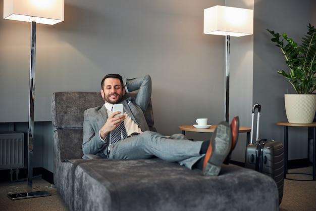 Uomo adulto felice che si riposa con uno smartphone