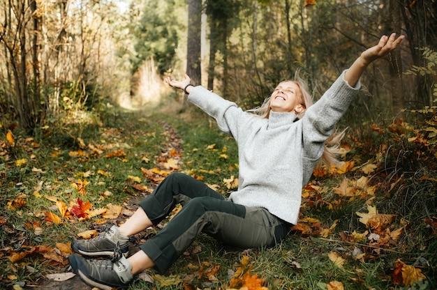 Felice donna adulta nella foresta di autunno