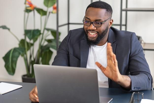 Felice uomo d'affari afroamericano in videoconferenza, parlando con i colleghi del processo di lavoro utilizzando il laptop, seduto alla scrivania, sorridente e agitando la mano