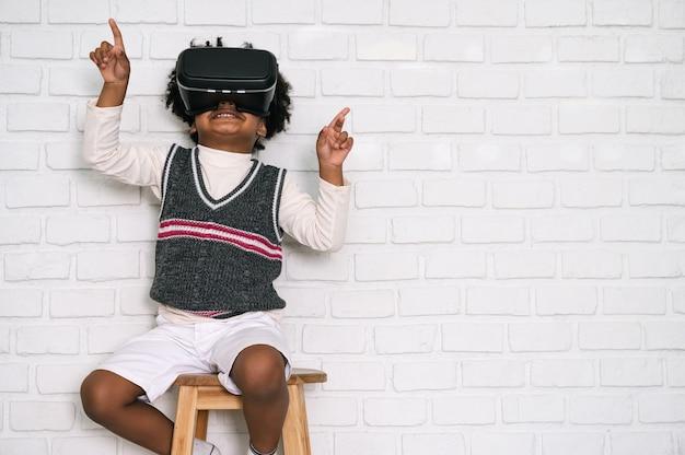 Felice bambino afroamericano con occhiali vr su uno sfondo di muro di mattoni bianchi