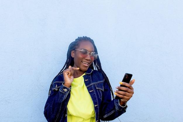 L'afroamericano felice comunica su uno smartphone su una parete blu