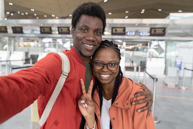 Felice coppia afro-americana prendendo selfie al terminal dell'aeroporto pronto per tornare alla normalità