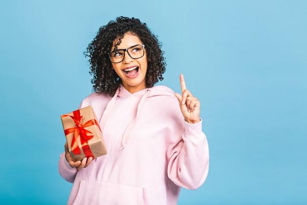 Signora riccia afroamericana felice nella risata casuale mentre tiene il contenitore di regalo presente isolato sopra fondo blu.