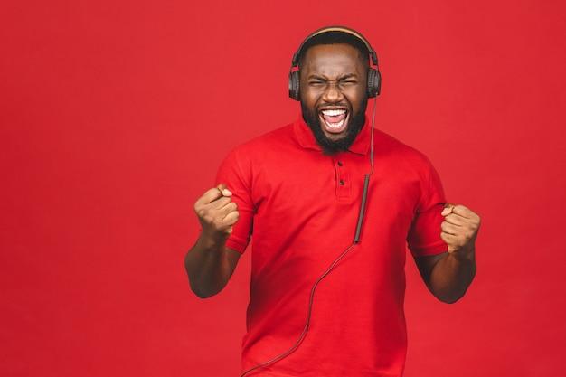Ragazzo di ballo afroamericano felice che gode della canzone dalle cuffie