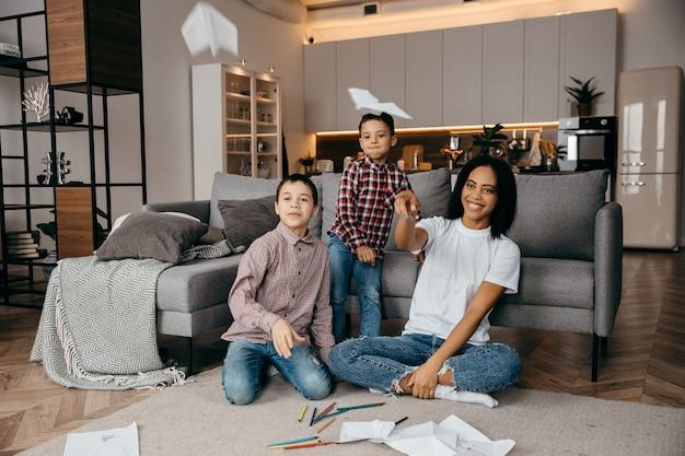 Felice madre di famiglia afroamericana e due figli che si divertono a casa e fanno volare aeroplani di carta