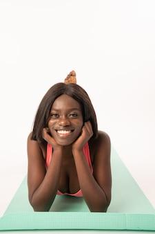 La ragazza afroamericana felice si trova sulla stuoia di yoga
