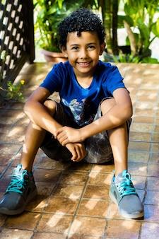 Felice bambino afroamericano seduto sul pavimento