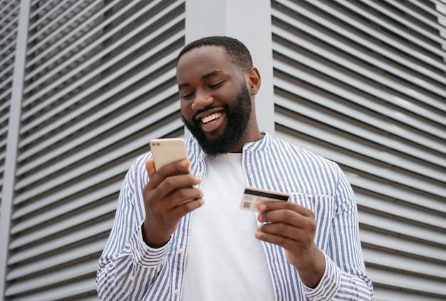 Uomo afroamericano felice che tiene la carta di credito, acquisti in linea