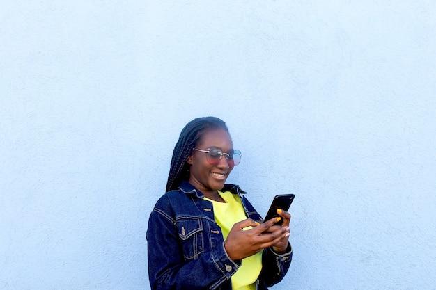 L'afroamericano felice con il telefono sulla parete blu
