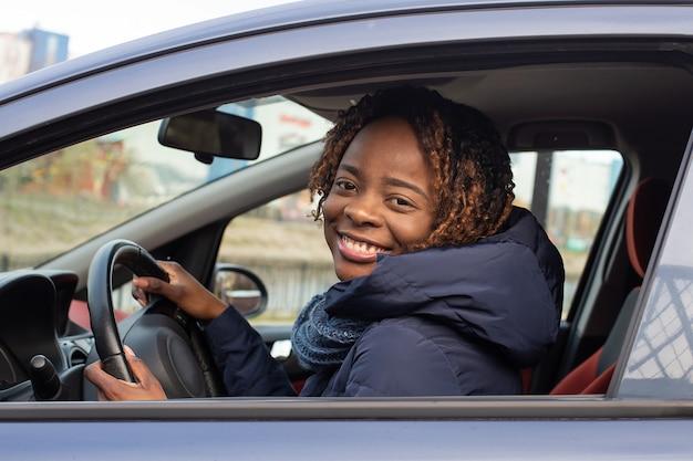 Felice donna afro-americana in auto guardando la fotocamera