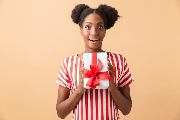 Felice donna afro-americana in abbigliamento casual che tiene presente casella con fiocco rosso, isolato