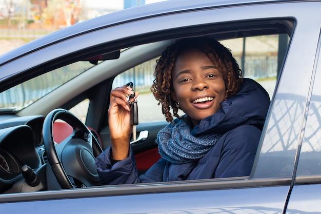 Felice donna afro-americana alla guida, noleggio auto