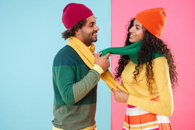Felice giovane coppia afroamericana in cappelli e sciarpe che flirtano l'uno con l'altro