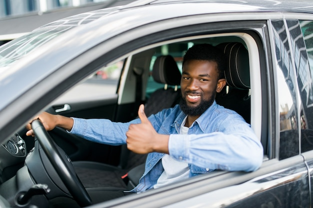 Uomo d'affari africano felice che dà pollice in su all'interno della nuova automobile
