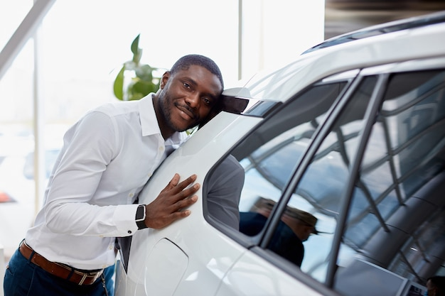 L'uomo d'affari africano felice abbraccia la sua nuova auto di lusso bianca in concessionaria