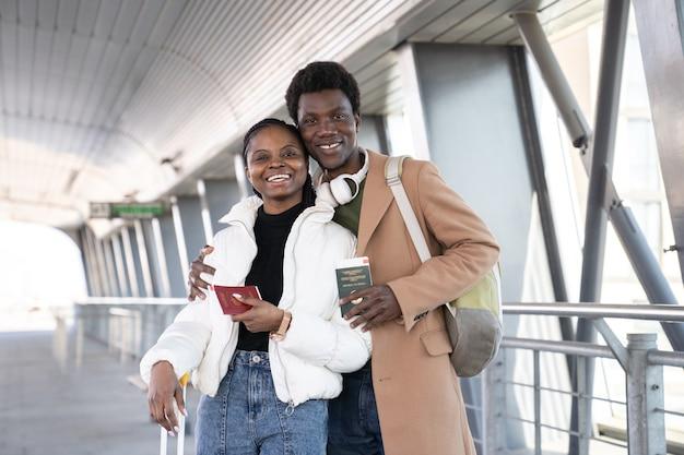 Felice coppia africana sorride e tiene i passaporti in aeroporto