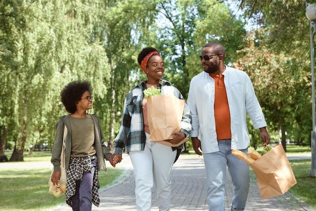 Felice coppia africana e il loro figlioletto tornano a casa dal supermercato