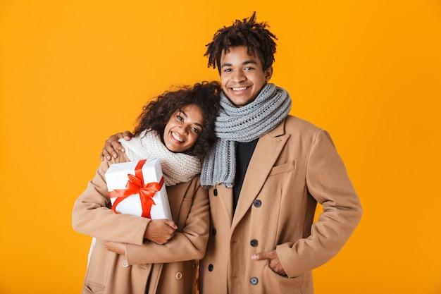 Felice coppia africana indossando abiti invernali in piedi isolato, dando regali