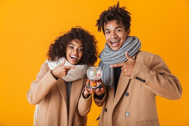 Felice coppia africana che indossa abiti invernali in piedi isolato, tenendo snowglobe