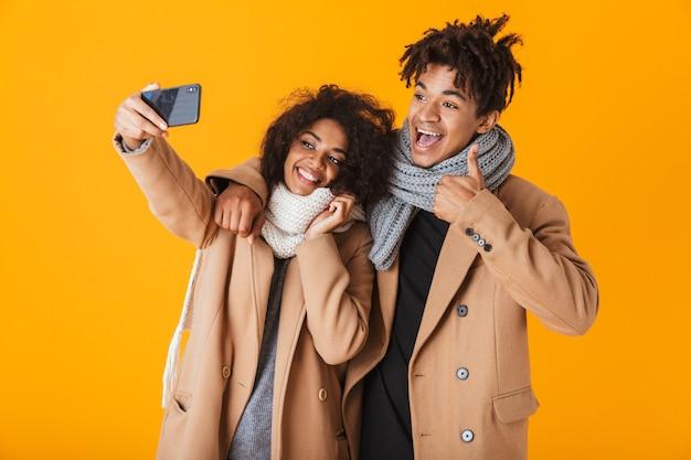 Felice coppia africana indossando abiti invernali in piedi isolato, prendendo un selfie