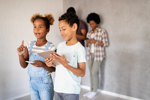 Famiglia africana felice che utilizza dispositivi digitali, tablet, smartphone. concetto di tecnologia