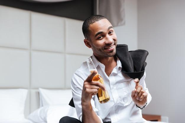 Felice l'uomo africano in camicia con la birra in mano che guarda l'obbiettivo nella camera d'albergo