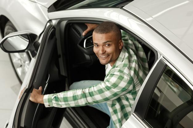 Uomo africano felice che sorride alla macchina fotografica, guardando fuori dalla nuova auto alla concessionaria.