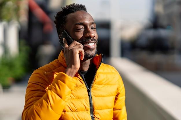 Uomo africano felice che parla su un telefono cellulare che cammina in una città con sfondo sfocato