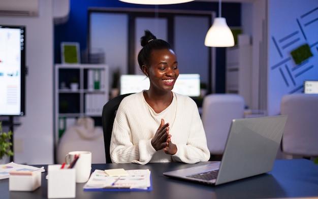 Felice africano sorridente a causa dei risultati positivi che lavorano la notte in ufficio commerciale