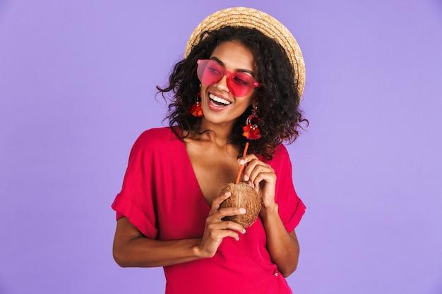 Felice donna africana in abito, cappello di paglia e occhiali da sole in posa con cocktail mentre guarda lontano oltre il muro viola