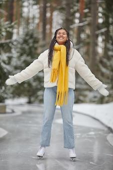 Felice donna africana in abiti caldi godendo il suo tempo sulla pista di pattinaggio in inverno